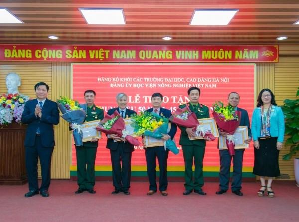 Đồng chí Vũ Tuấn Dũng và đồng chí Nguyễn Thị Lan trang trọng gắn Huy hiệu Đảng, trao Quyết định và tặng hoa chúc mừng các đồng chí vinh dự được nhận Huy hiệu Đảng