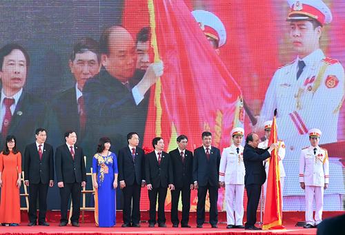 Thủ tướng gắn Huân chương Hồ Chí Minh lên lá cờ truyền thống của Học viện Nông nghiệp Việt Nam. Ảnh: VGP/Quang Hiếu