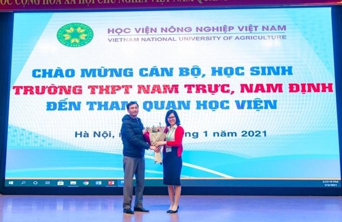ThS. Đỗ Thị Kim Hương - Phó Giám đốc Trung tâm Quan hệ công chúng và Hỗ trợ sinh viên tặng hoa đại diện Trường THPT Nam Trực, Nam Định